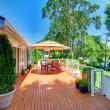 Large orange deck with umbrella and house and railing. — Stock Photo #8751452