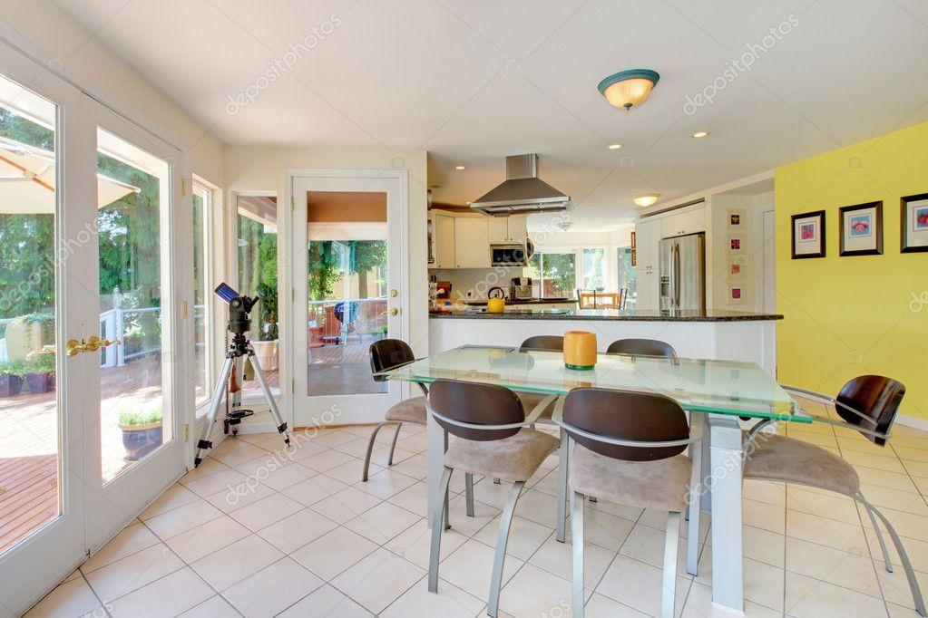 Tavolo sala da pranzo con cucina dietro e muro giallo — Foto Stock ...