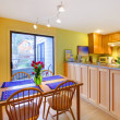 Yellow happy dining table and apartment kitchen — Stock Photo
