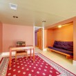Basement room with desk and sofa in orange. - Photo