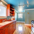 Blue kitchen with cherry cabinets and shiny floor. - Zdjcie stockowe