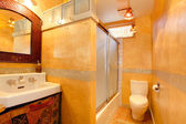 Exotic orange artistic bathroom with antique sink — Stock Photo
