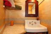 Antique sink with faux orange wall and mirror — Stock Photo