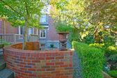 Jardim inglês em casa, com casa de tijolo — Foto Stock