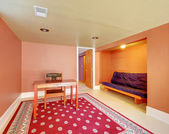 Basement room with desk and sofa in orange. — Stock Photo