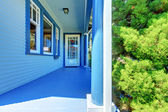 Blue house covered front porch with entrance door. — Stock Photo