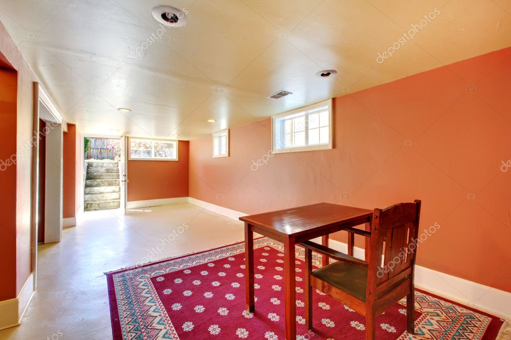 large basement room with desk and orange walls stock photo