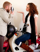 Photographer and a beautiful woman on the scooter. — Stock Photo