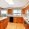 Stock Photo: Bright wood cozy kitchen with water view and white countertop.
