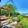 Private home Garden with a swinging bench near the lake. — Stock Photo #9288921
