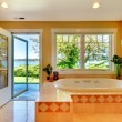 Yellow bathroom with lake view and large tub. — Stock Photo