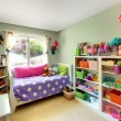 Girls bedroom with many toys and purple bed. — Zdjęcie stockowe #9289243