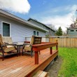 Grey small house with simple deck and outdoor chairs. - Stock Photo