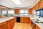 Bright wood cozy kitchen with water view and white countertop. — ストック写真