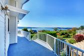 Ytterdörr veranda med utsikt över vattnet och grå huset och bush grönska. — Stockfoto