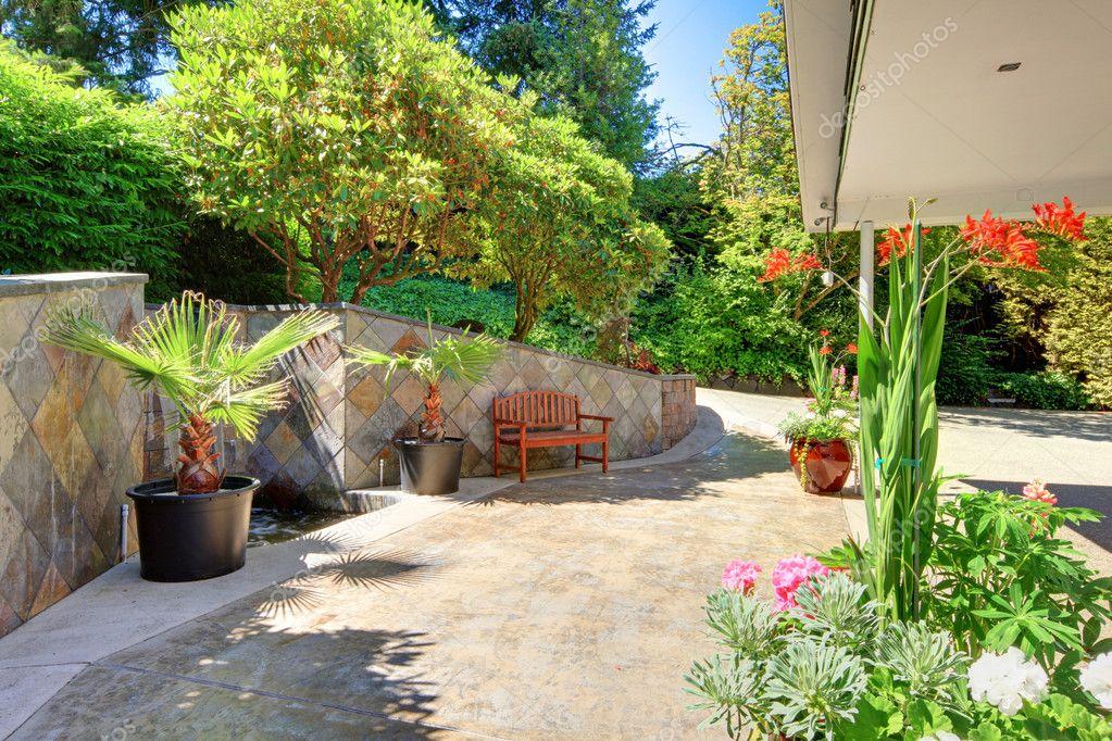 flores jardim exterior : flores jardim exterior:jardim exterior de casa com flores e telhas cerâmicas — Foto Stock