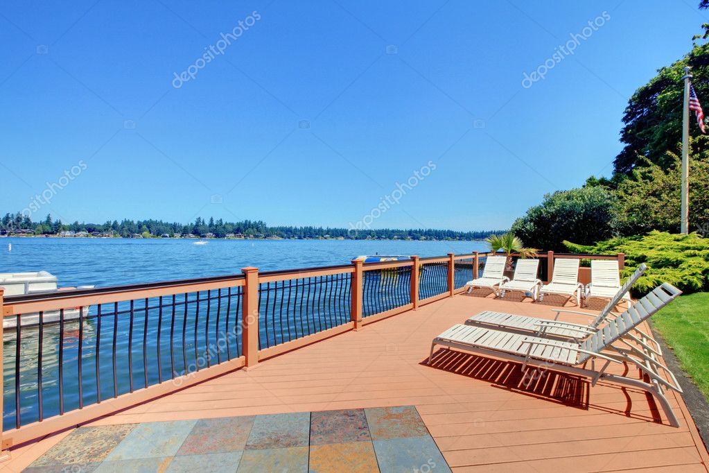 Beautiful large deck near the lake with  chairs and landscape.  Stock Photo #9289110