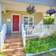 Grey old house front porch exterior with red door. — Stock Photo #9333521