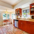 Charming cherry wood kitchen with tile floor. — Stock Photo