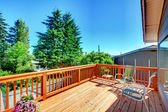 Large new wood deck home exterior with chairs. — Stock Photo