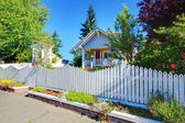 Cute old grey house behind white fence. — Stock Photo