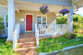 Grey old house front porch exterior with red door. — Stock Photo