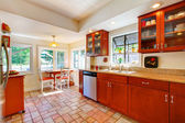 Charming cherry wood kitchen with tile floor. — Photo