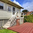 Small grey house with staircase to back yard deck. — Stock Photo