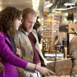 Young couple exploring and shopping indoor market. — Stock Photo