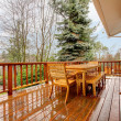 Stock Photo: Wood deck with furniture and grey house.