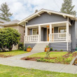 Grey craftsman style house with white porch. - Stock Photo