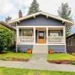 Small blue house with white porch exterior. - Stock Photo