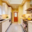 Yellow and white narrow modern kitchen. - Stock Photo