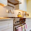 Yellow kitchen with white cabinets and stove. - Stock Photo