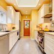 Stock Photo: Yellow kitchen with white cabinets and stove.
