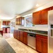 Stock Photo: Large bright kitchen with dark cherry cabinets.