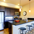 Modern brown kitchen with bar and stools. — Stock Photo