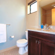 Small blue bathroom with wood cabinet. — Stock Photo