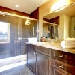 Bathroom with wood cabinet and glass shower. — Stock Photo