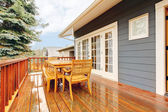 Wood deck with furniture and grey house. — Stock Photo
