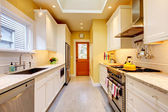 Yellow and white narrow modern kitchen. — Stock Photo
