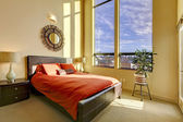 Large high ceiling bedroom with red bed. — Stock Photo