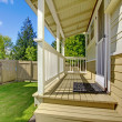Stock Photo: Back yard with porch and beige house.