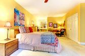 Velké žluté ložnice s červeným postelí. — Stock fotografie