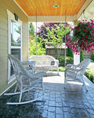 Front porch with white furniture and flowers. — Stock Photo