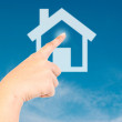 Royalty-Free Stock Photo: Hand pushing home icon on the blue sky field.
