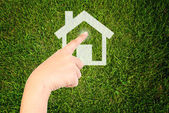Hand pushing home icon on the grass field. — Stock Photo