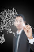 Businessman drawing Chinese Style dragon statue. — Stock Photo