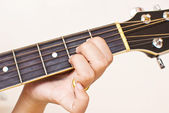 Hand pressing classic acoustic guitar chord. — Stock Photo