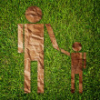 Vintage man and child symbol on the grass field. — Stock Photo #10494753